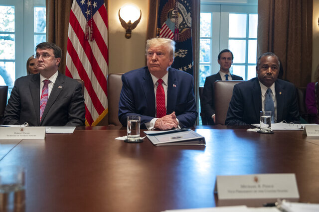 Secretary of Veterans Affairs Robert Wilkie, left, and Secretary of Housing and Urban Development Ben Carson, right, listen as President Donald Trump speaks during a cabinet meeting at the White House, Tuesday, Nov. 19, 2019, in Washington. (AP Photo/ Evan Vucci)