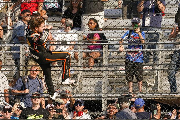 Noah Gragson (9) climbs the fence as he celebrates winning the NASCAR Xfinity auto race in Richmond, Va., Saturday, Sept. 11, 2021. (AP Photo/Steve Helber)