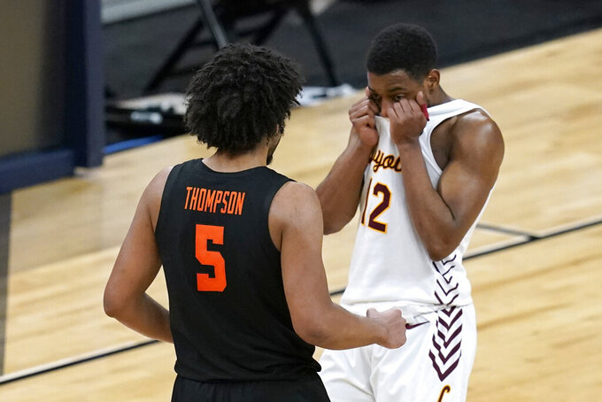 Loyola Chicago guard Marquise Kennedy (12) walks off the court in front of Oregon State guard Ethan Thompson (5) at the end of a Sweet 16 game in the NCAA men's college basketball tournament at Bankers Life Fieldhouse, Saturday, March 27, 2021, in Indianapolis. Oregon State won 65-58. (AP Photo/Darron Cummings)