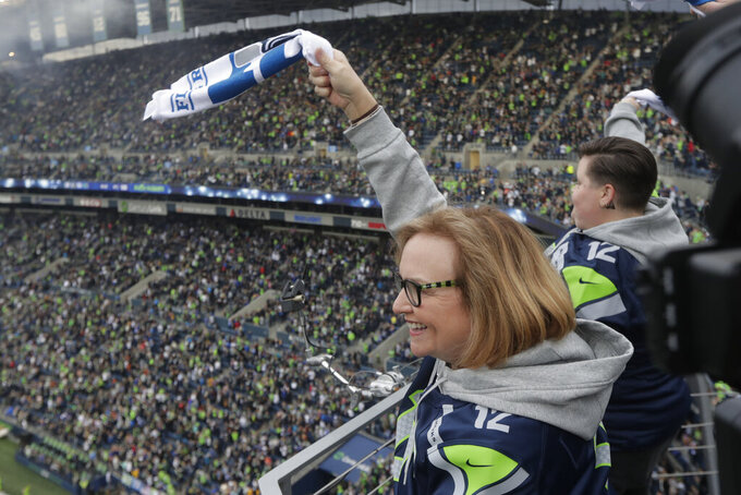 Seattle Seahawks owner Jody Allen waves a towel before the team's NFL football game against the Los Angeles Rams, Thursday, Oct. 3, 2019, in Seattle. (AP Photo/Stephen Brashear)