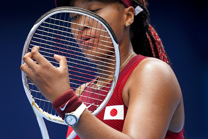 FILE - In this July 26, 2021 file photo, Naomi Osaka, of Japan, adjusts her racket during a second round tennis match against Viktorija Golubic, of Switzerland, at the 2020 Summer Olympics, in Tokyo, Japan. Osaka and Simone Biles are prominent young Black women under the pressure of a global Olympic spotlight that few human beings ever face. But being a young Black woman -- which, in American life, comes with its own built-in pressure to perform -- entails much more than meets the eye. (AP Photo/Patrick Semansky, File)