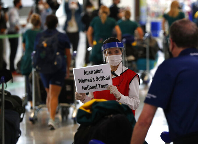 A woman wearing protective mask and face shield greets members of Australia's Olympic softball squad on their arrival at Narita international airport in Narita, east of Tokyo, Japan Tuesday, June 1, 2021. Australia's Olympic softball squad touched down in Japan on Tuesday and was among the earliest arrivals for the Tokyo Games. (Issei Kato/Pool Photo via AP)