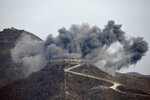 FILE - In this Nov. 15, 2018, file photo, smoke from an explosion rises as part of the dismantling of a South Korean guard post in the Demilitarized Zone dividing the two Koreas in Cheorwon, South Korea, as a North Korean guard post sits high in the upper left. On both sides of the world's most heavily armed border Thursday, June 25, 2020, solemn ceremonies will mark the 70th anniversary of the outbreak of a war that killed and injured millions, left large parts of the Korean Peninsula in rubble and technically still continues. (Jung Yeon-je/Pool Photo via AP, File)