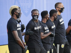 Members of the Columbus Crew, wearing shirts and masks with messages about race, stand on the field before an MLS soccer match Wednesday, July 8, 2020, in Kissimmee, Fla. (AP Photo/John Raoux)