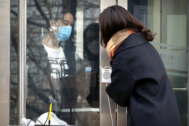 A clerk wearing a face mask talks with a customer through the doors of a stock brokerage which was closed except for limited transactions conducted through the glass of its front doors in Beijing, Friday, Feb. 21, 2020. Asian stock markets followed Wall Street lower Friday after a spike in new virus cases in South Korea refueled investor anxiety about China's disease outbreak. (AP Photo/Mark Schiefelbein)