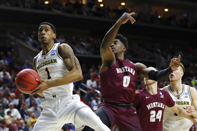 Michigan guard Charles Matthews drives to the basket past Montana guard Michael Oguine, right, during a first round men's college basketball game in the NCAA Tournament, Thursday, March 21, 2019, in Des Moines, Iowa. (AP Photo/Charlie Neibergall)