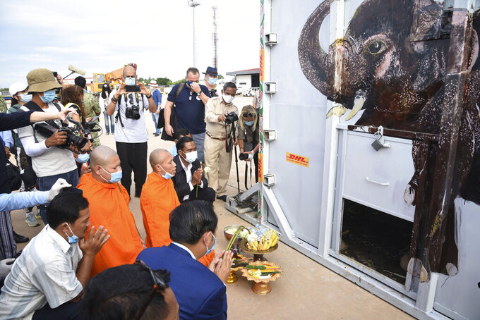 """The container holding Kaavan the elephant is blessed by monks during its arrival from Pakistan at the Siem Reap International Airport, Cambodia, Monday, Nov. 30, 2020. Kaavan, dubbed the """"world's loneliest elephant"""" after languishing alone for years in a Pakistani zoo, has arrived in Cambodia where a sanctuary with the much-needed company of other elephants awaits him. (Pool Photo via AP)"""