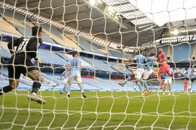 Real Madrid's Karim Benzema scores his side's first goal during the Champions League, round of 16, second leg soccer match between Manchester City and Real Madrid at the Etihad Stadium in Manchester, England, Friday, Aug. 7, 2020. (Peter Powell/Pool Photo via AP)