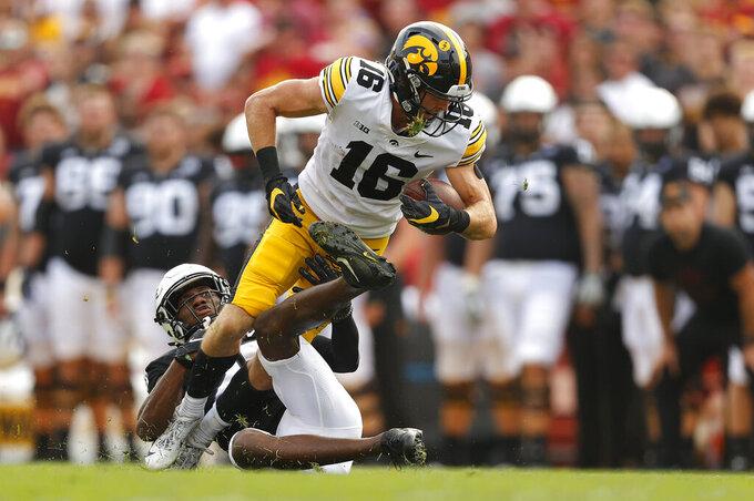 Iowa State defensive back T.J. Tampa (25) pulls down Iowa wide receiver Charlie Jones (16) during the first half of an NCAA college football game, Saturday, Sept. 11, 2021, in Ames, Iowa. Iowa won 27-17. (AP Photo/Matthew Putney)