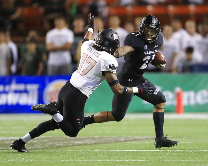 Hawaii running back Fred Holly III (21) stiff arms UNLV defensive back Evan Austrie (17) during the first quarter of an NCAA college football game, Saturday, Nov. 17, 2018, in Honolulu. (AP Photo/Marco Garcia)