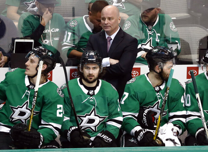 FILE- In this April 17, 2019, file photo, Dallas Stars coach Jim Montgomery, center rear, watches play against the Nashville Predators during the third period of Game 4 in an NHL hockey first-round playoff series in Dallas. The St. Louis Blues have hired Jim Montgomery as an assistant 10 months after he was fired as coach of the Dallas Stars for unprofessional conduct. (AP Photo/Tony Gutierrez, File)