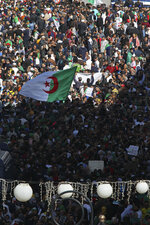 Algerian demonstrators take to the streets in the capital Algiers to protest against the government, in Algeria, Friday, Nov. 1, 2019. Police struggled Friday to contain thousands of Algerian demonstrators surging through the streets of the capital to protest next month's presidential election and celebrate 65 years since Algeria's war for independence from France. (AP Photo/Fateh Guidoum)