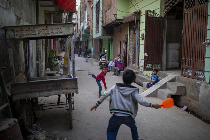 Children play in an alleyway in North Ghonda neighborhood, one of the worst riot affected area during the February 2020 communal riots, in New Delhi, India, Friday, Feb. 19, 2021. As the first anniversary of bloody communal riots that convulsed the Indian capital approaches, Muslim victims are still shaken and struggling to make sense of their struggle to seek justice. (AP Photo/Altaf Qadri)