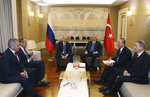 Turkish President Recep Tayyip Erdogan, rear right, Russian President Vladimir Putin, rear left, Russia's Defence Minister Sergei Shoigu, left, Russia'a Foreign Minister Sergey Lavrov, second left, Turkey's Defence Minister Hulusi Akar, right, and Turkish Foreign Minister Mevlut Cavusoglu speak during a meeting after a ceremony for a dual natural gas line, TurkStream, connecting Russia and Turkey, in Istanbul, Wednesday, Jan. 8, 2020. Lavrov and Cavusoglu said that Turkish and Russian presidents call for a cease-fire in Libya to start on Jan. 12.(Presidential Press Service via AP, Pool)