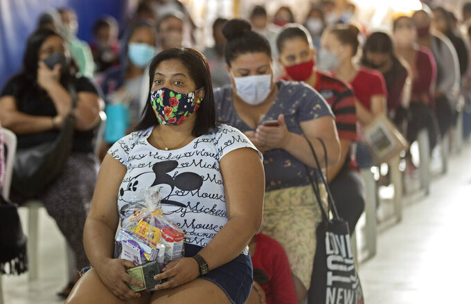 """Women and girls sit after receiving a donation of sanitary napkins and other female hygiene supplies provided by the local NGO """"G10 Favelas"""" amid the COVID-19 pandemic in the favela of Paraisopolis, in Sao Paulo, Brazil, Monday, May 24, 2021. (AP Photo/Andre Penner)"""