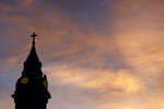 FILE - In this Sept. 27, 2015, file photo, clouds are lit by the rising sun over St. Augustine Roman Catholic Church in Philadelphia. Pennsylvania's high court has dealt a blow to victims of child sexual abuse who are trying to revive their otherwise outdated claims. The court on Wednesday, July 21, 2021, tossed a lawsuit by a woman whose earlier legal victory had given hope to other victims who sued in the wake of a landmark report that documented decades of child molestation within the Catholic church in Pennsylvania. (AP Photo/Julio Cortez, File)
