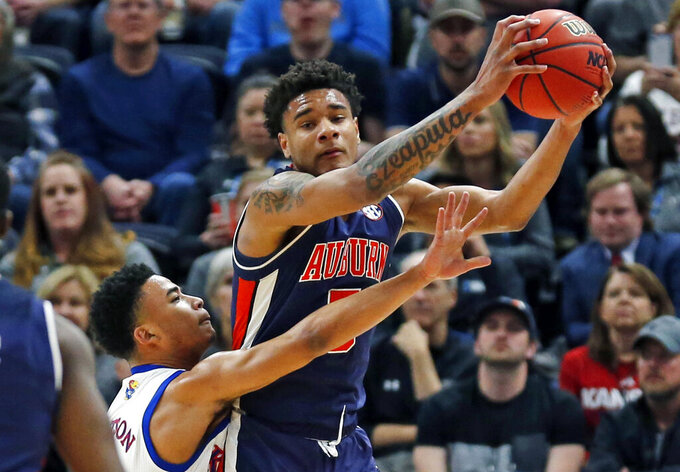 Kansas guard Devon Dotson, left, guards Auburn forward Chuma Okeke during the first half of a second-round game in the NCAA men's college basketball tournament Saturday, March 23, 2019, in Salt Lake City. (AP Photo/Rick Bowmer)