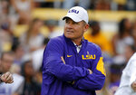 FILE - Then-LSU head coach Les Miles watches his team warm up before an NCAA college football game against Florida in Baton Rouge, La., in this Saturday, Oct. 17, 2015, file photo. In a $50 million federal racketeering lawsuit, an associate athletic director at LSU accuses university officials of retaliating against her for reporting racist remarks and inappropriate sexual behavior by former head football coach Les Miles. (AP Photo/Gerald Herbert, File)