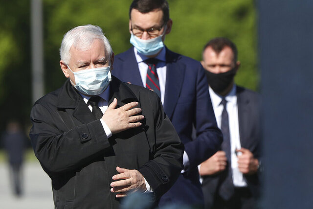 Poland's ruling party leader Jaroslaw Kaczynski, left, and Prime Minister Mateusz Morawiecki, center, wearing masks, pray at the monument to the late President Lech Kaczynski, the party leader's twin, killed with 95 others in a plane crash April 10, 2010 in Russia, in Warsaw, Poland Sunday, May 10, 2020. Poland was to hold presidential election Sunday but the anti-coronavirus lockdown and political infighting made it impossible and there is no voting. (AP Photo/Czarek Sokolowski)