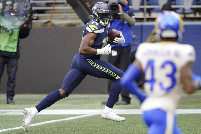 Seattle Seahawks wide receiver DK Metcalf, left, heads to the end zone to score against the Los Angeles Rams on a 51-yard pass reception during the first half of an NFL wild-card playoff football game, Saturday, Jan. 9, 2021, in Seattle. (AP Photo/Ted S. Warren)