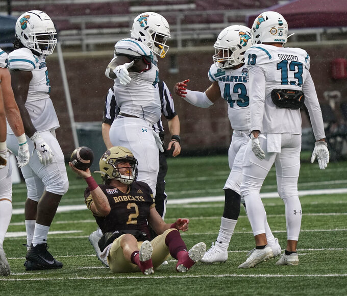Texas State's Brady McBride (2) reacts as Coastal Carolina players including Enock Makonzo (43) and Mateo Sudipo (13) celebrate a sack during the second half of an NCAA college football game in San Marcos, Texas, Saturday, Nov. 28, 2020. (AP Photo/Chuck Burton)