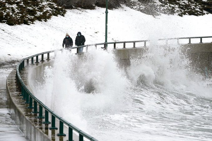 Two men walk along Lynn Shore Reservation as surf kicks up in the aftermath of a snowstorm, Tuesday, Feb. 2, 2021, in Lynn, Mass. A sprawling, lumbering winter storm has walloped the Eastern U.S., shutting down coronavirus vaccination sites, closing schools and halting transit. (AP Photo/Elise Amendola)