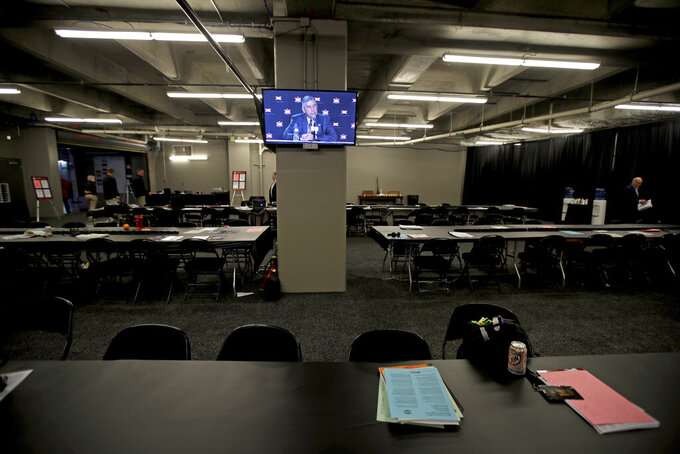Big 12 commissioner Bob Bowlsby is displayed on a monitor in an empty media room as he talks to the media after canceling the remaining NCAA college basketball games in the Big 12 Conference tournament due to concerns about the coronavirus Thursday, March 12, 2020, in Kansas City, Mo. (AP Photo/Charlie Riedel)