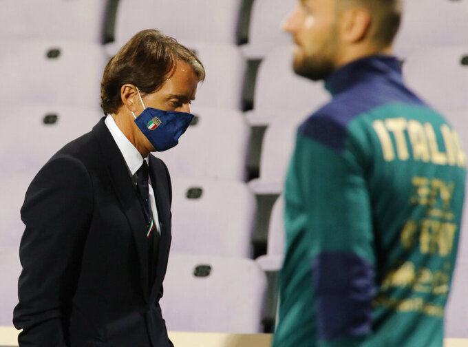 """FILE - In this Wednesday, Oct. 7, 2020 file photo, Italy's coach Roberto Mancini wears a face mask during the international friendly soccer match between Italy and Moldova, at the Artemio Franchi stadium, in Florence, Italy. Italy coach Roberto Mancini has tested positive for the coronavirus days before the international break. The Italian soccer federation says that Mancini is """"completely asymptomatic"""" and is self-isolating at his house in Rome. The Italy squad will meet up on Sunday. It plays an international friendly against Estonia on Wednesday and hosts Poland in the Nations League four days later. (Marco Bucco/LaPresse via AP)"""