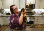 Victoria Sinclaire holds her cat Toby, that survived the Camp Fire, as her dog Joey looks on at her recently rebuilt home in Paradise, Calif., Tuesday, Nov. 5, 2019. Unable to get Toby and another of her pet cats, it took Sinclaire six hours to escape the flames from last year's wildfire that destroyed 90 percent of Paradise. (AP Photo/Rich Pedroncelli)