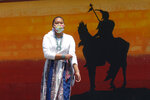 Lemiley Lane, a Bountiful junior who grew up in the Navajo Nation in Arizona, walks along the campus near a a mural of an Indigenous man meant to represent the Braves mascot at Bountiful High School, July 21, 2020, in Bountiful, Utah. While advocates have made strides in getting Native American symbols and names changed in sports, they say there's still work to do mainly at the high school level, where mascots like Braves, Indians, Warriors, Chiefs and Redskins persist. (AP Photo/Rick Bowmer)