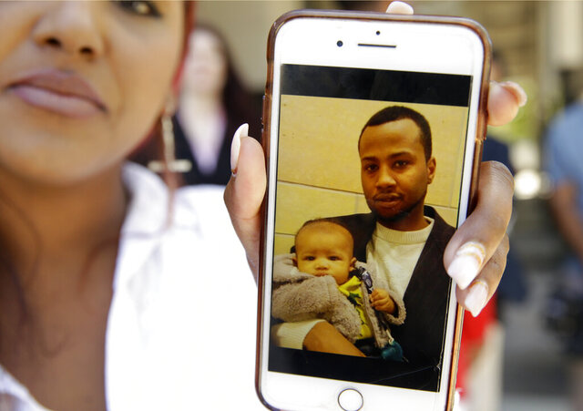 FILE - In this June 27, 2018, file photo Cassius Hudson displays her phone with a photo of her son, Noah McIntyre, held by his father, Mikel McIntyre, during a news conference in Sacramento, Calif. The Sacramento County Sheriff's Office has released the investigative file on the 2017 shooting of Mikel McIntyre, that concluded the killing was justified, contradicting a county finding that excessive force was used. Deputies fired 28 shots at McIntyre as he ran from them in Rancho Cordova after hurling rocks at deputies, injuring one. The Sacramento Bee says Sheriff Scott Jones released 1,193 documents along with photos and videos. The file was released in the midst of public outcry over the death of another unarmed black man, George Floyd, in police custody this week in Minneapolis. (AP Photo/Rich Pedroncelli, File)