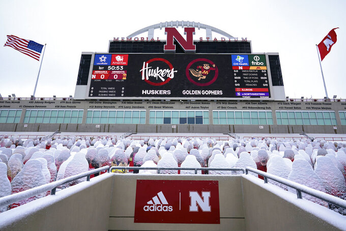 Snow-covered cutouts of fans are seen in the stands prior to an NCAA college football game between Nebraska and Minnesota, in Lincoln, Neb., Saturday, Dec. 12, 2020. (AP Photo/Nati Harnik)