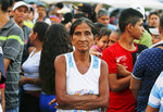 A woman poses for a photo as she lines up to receive bags with food subsidized by Venezuelan President Nicolas Maduro's government near the international bridge of Tienditas on the outskirts of Urena, Venezuela, Monday, Feb. 11, 2019, on the border with Colombia. Nearly three weeks after the Trump administration backed an all-out effort to force Maduro out, the embattled socialist leader is holding strong and defying predictions of an imminent demise. (AP Photo/Fernando Llano)