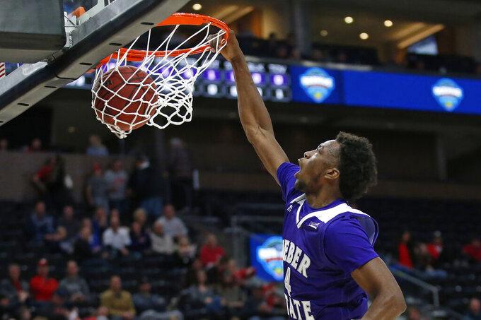 Weber State guard Kham Davis (4) dunks the ball against Utah in the first half during an NCAA college basketball game Saturday, Dec. 14, 2019, in Salt Lake City. (AP Photo/Rick Bowmer)