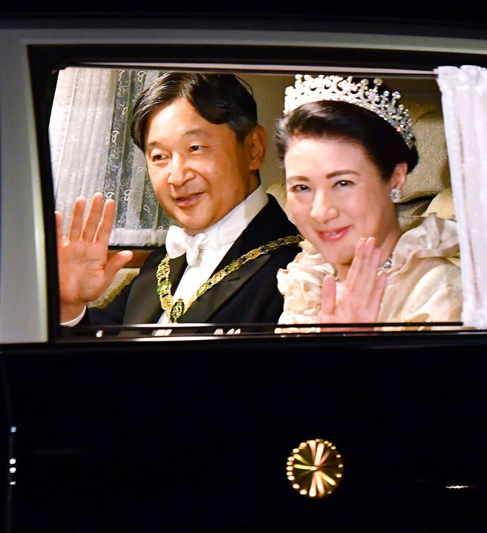 Japan's Emperor Naruhito, left, and Empress Masako, right, wave, as they depart for the Imperial Palace for the court banquet, in Tokyo, Tuesday, Oct. 22, 2019.  Japan's Naruhito proclaimed himself Emperor during an enthronement ceremony at the Imperial Palace, declaring himself the country's 126th monarch.(Ren Onuma/Kyodo News via AP)