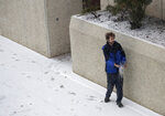 Employee Dustin Zoglman throws salt on a slippery walkway in front of the Red Lion Hotel Paper Valley Wednesday, Nov. 13, 2019, in Appleton, Wis. (Dan Powers/The Post-Crescent via AP)