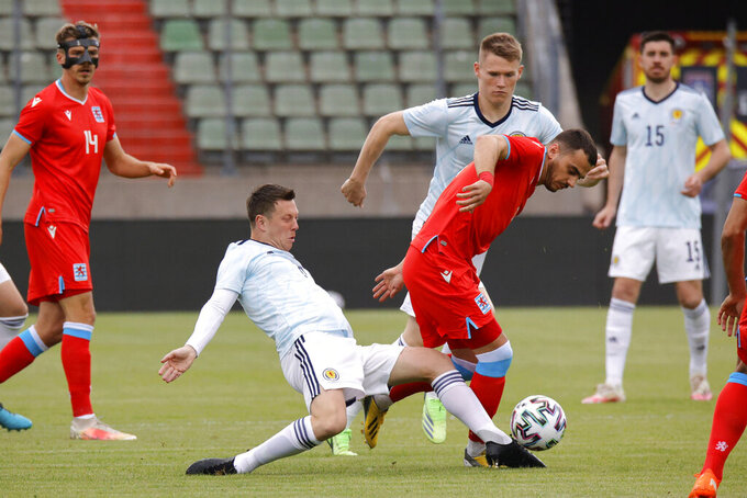 Scotland's Callum McGregor, left, fights for the ball with Luxembourg's Danel Sinani during the international friendly soccer match between Luxembourg and Scotland at the Josy Barthel Stadium in Luxembourg, Sunday, June 6, 2021. (AP Photo/Olivier Matthys)