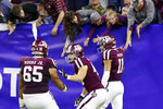 Texas A&M offensive lineman Dan Moore Jr. (65) and tight end Ryan Renick, middle, celebrate as quarterback Kellen Mond (11) high-five fans in the stands after Mond's touchdown during the second half of the Texas Bowl NCAA college football game against Oklahoma State on Friday, Dec. 27, 2019, in Houston. (AP Photo/Michael Wyke)