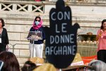 """A banner reading """"with Afghan women"""" is seen as an Afghan refugee, who denied to give her name for safety reasons, delivers her speech during a demonstration in favor of Afghan women's rights, staged by women rights activists, in Rome, Saturday, Sept. 25, 2021. (AP Photo/Andrew Medichini)"""