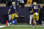 Notre Dame quarterback Ian Book (12) celebrates his 7-yard touchdown run with wide receiver Chase Claypool (83) during the second half of an NCAA college football game against Virginia Tech, Saturday, Nov. 2, 2019, in South Bend, Ind. (AP Photo/Carlos Osorio)