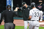 Chicago White Sox manager Rick Renteria, center, is ejected from a baseball game by umpire Dan Bellino for arguing after James McCann (33) was called out on strikes during the ninth inning Monday, Sept. 21, 2020, in Cleveland. (AP Photo/Ron Schwane)