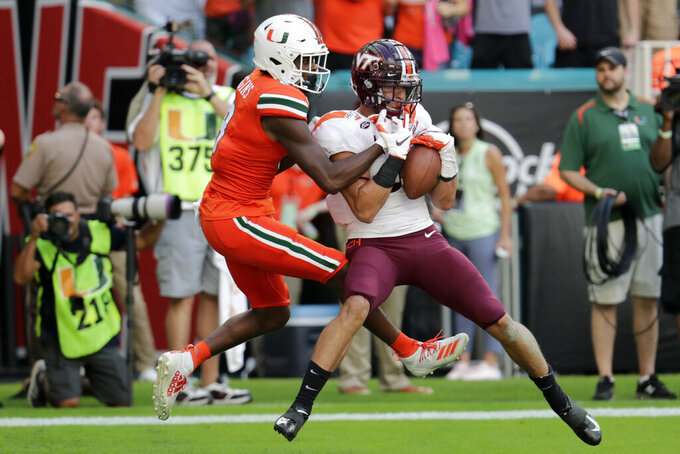 File-This Oct. 5, 2019, file photo shows Virginia Tech defensive back Caleb Farley, right, intercepting a pass intended for Miami wide receiver Dee Wiggins, left, during the first half of an NCAA college football game,  in Miami Gardens, Fla.  Farley was the first top prospect to make the decision that has added a whole new layer of uncertainty to the annual crapshoot that is the NFL draft. (AP Photo/Lynne Sladky, File)