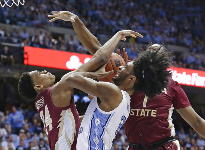 North Carolina's Coby White tries to shoot as Florida State's Devin Vassell (24) and Raiquan Gray (1) defend during the first half of an NCAA college basketball game in Chapel Hill, N.C., Saturday, Feb. 23, 2019. (AP Photo/Gerry Broome)
