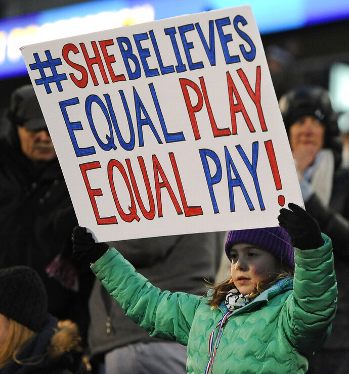 FILE - In this April 6, 2016, file photo, a girl holds up a sign for equal pay for the U.S. women soccer players, during the first half of an international friendly soccer match between the United States and Colombia, in East Hartford, Conn. Players for the World Cup champion women's national team say mediation talks with the U.S. Soccer Federation over equal pay are over. Molly Levinson, who represents the players in matters concerning the dispute, said in a statement Wednesday, Aug. 14, 2019, that the players look forward to a jury trial. (AP Photo/Jessica Hill, File)