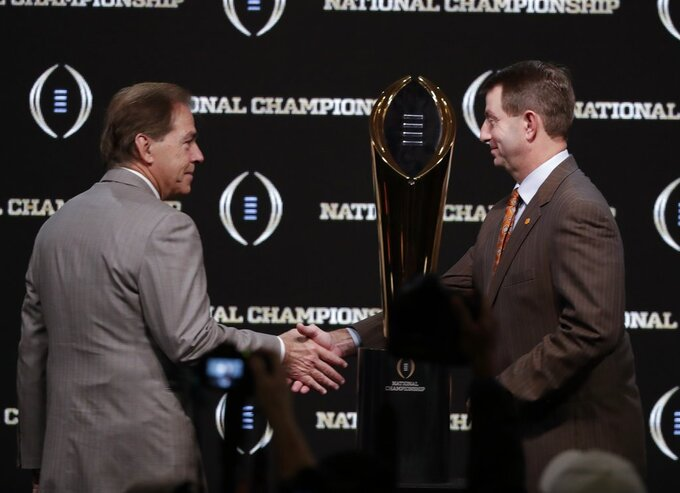 Alabama head coach Nick Saban and Clemson head coach Dabo Swinney pose with the trophy at a news conference for the NCAA college football playoff championship game Sunday, Jan. 6, 2019, in Santa Clara, Calif. (AP Photo/Chris Carlson)
