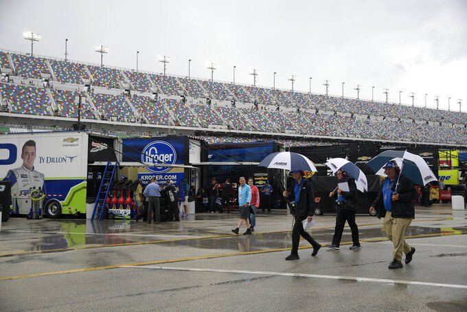 Officials walk through the garage area during a rain delay before a NASCAR Cup Series auto race at Daytona International Speedway, Saturday, July 6, 2019, in Daytona Beach, Fla. (AP Photo/Phelan M. Ebenhack)