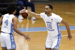 North Carolina guard R.J. Davis (4) congratulates forward Garrison Brooks (15) following Brooks' basket against Duke during the second half of an NCAA college basketball game in Chapel Hill, N.C., Saturday, March 6, 2021. (AP Photo/Gerry Broome)