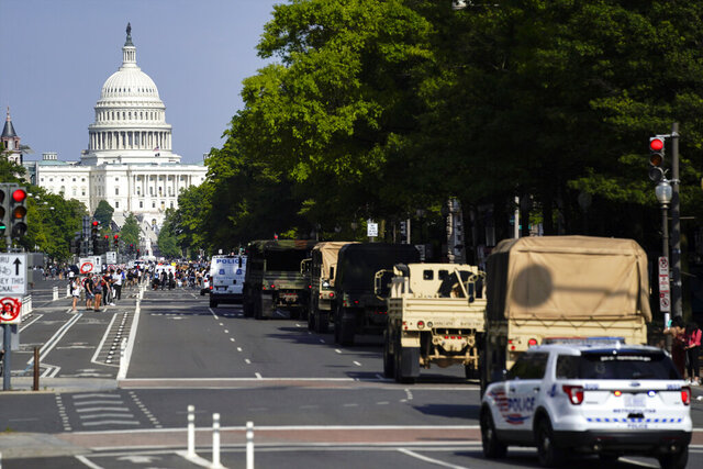 Demonstrators walk along Pennsylvania Avenue as a line of police and military vehicles drive as they protest the death of George Floyd, Wednesday, June 3, 2020, in Washington. Floyd died after being restrained by Minneapolis police officers. (AP Photo/Evan Vucci)
