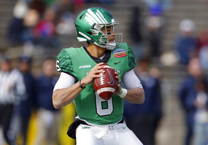 FILE - In this Dec. 15, 2018, photo, North Texas quarterback Mason Fine looks to throw a pass during the first half of the New Mexico Bowl NCAA college football game against Utah State in Albuquerque, N.M. North Texas is favored to win West Division in Conference USA. Fine began his first camp way down on the depth chart--maybe sixth or seventh behind the transfer quarterback who did start the first game of the 2016 season. But Fine got into the opener as a true freshman, and has been UNT's starter since taking that role his second game. (AP Photo/Andres Leighton, File)