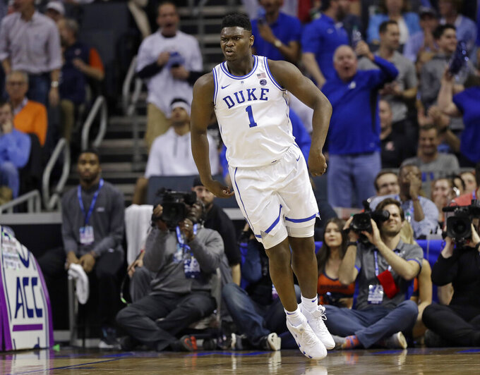 Duke's Zion Williamson (1) reacts after a dunk against Syracuse during the first half of an NCAA college basketball game in the Atlantic Coast Conference tournament in Charlotte, N.C., Thursday, March 14, 2019. (AP Photo/Chuck Burton)
